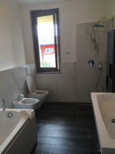 Rivestimento gres effetto marmo e pavimento gres effetto legno con piatto doccia in piastrella.
